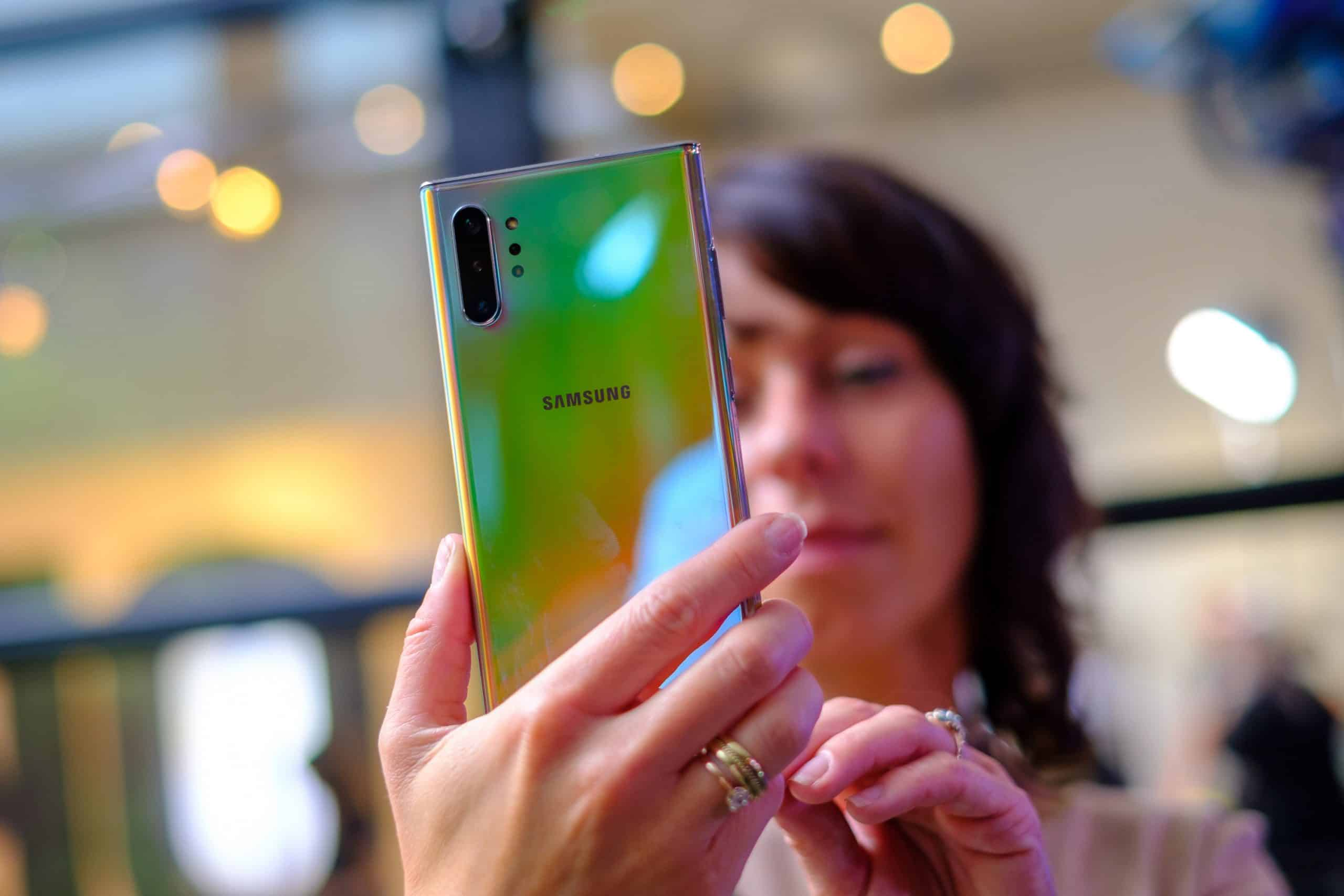 Woman holding the Galaxy Note 10 showing the Aura Glow color